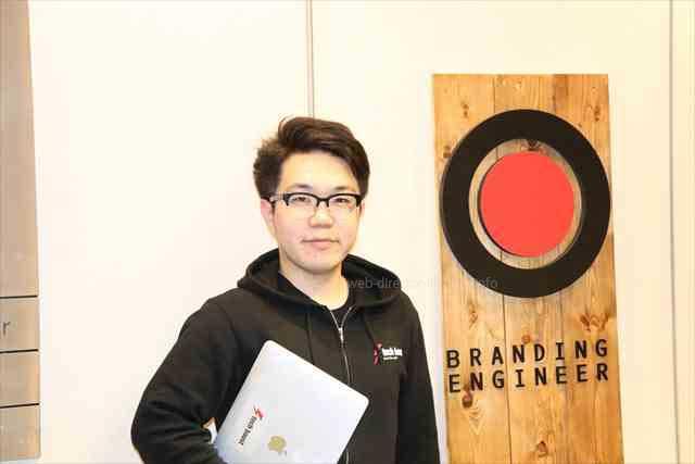 株式会社branding engineerの入り口にて、TECH BOOST(テックブースト)校長の山口偉大さんの写真
