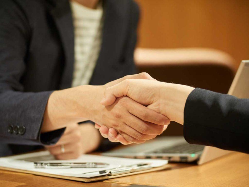 フリーランス人材とエージェント担当者が握手するイメージ写真